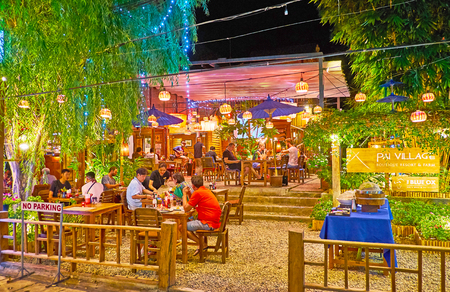 PAI, THAILAND - MAY 5, 2019: The crowded cafe with large outdoor terrace in Walking street of Night Market, on May 5 in Pai