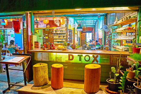 PAI, THAILAND - MAY 5, 2019: The small cozy tourist bar with utdoor counter with log sits, located in Walking street of Night Market, on May 5 in Pai