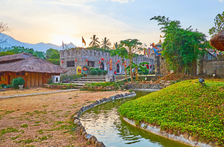 SANTICHON, THAILAND - MAY 5, 2019: Watch the sunset over the mountains and scenic fortress-like building of Chinese Cultural Center of Yunnan tea village, on May 5 in Santichon