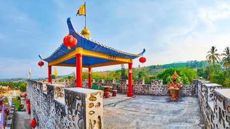 SANTICHON, THAILAND - MAY 5, 2019: The top terrace of the fortress has cozy shady Chinese pavilion with sweeping roof, slender pillars and red lanterns, on May 5 in Santichon
