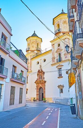 The modest facade of San Felipe Neri Parish Church with two bell towers and beautiful carved door frame, Malaga, Spain