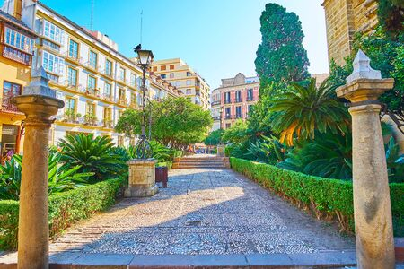 The medieval stone columns at the entrance to the scenic Cathedral garden, located in Calle Cister (street), Malaga, Spain