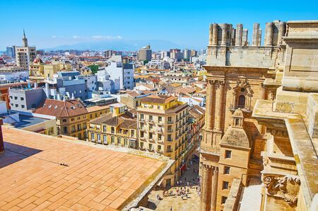 Malaga Cathedral roof observes unfinished stone right bell tower, rising over the city roofs, Andalusia, Spain