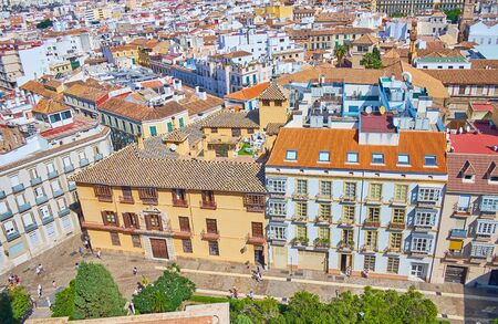 The red tile roofs of old Malaga and the colorful roof of Baroque style Zea Salvatierra palace from the top of Cathedral, Spain