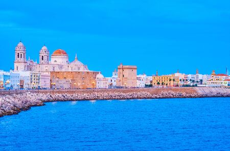 The curves seashore of old Cadiz with amazing evening illumination of medieval Cathedral and small houses on the shore line, Spain