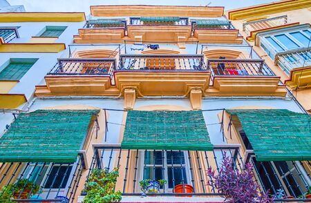The old multi-storey residential house with balconies covered with old-fashioned wooden rolling curtains, Cadiz, Spain