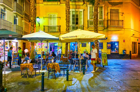 CADIZ, SPAIN - SEPTEMBER 19, 2019: The romantic dinner in a small outdoor restaurant in cozy Antonio Martin square in surrounding of medieval Andalusian style houses, on September 19 in Cadiz