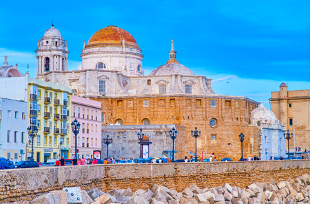 CADIZ, SPAIN - SEPTEMBER 19, 2019: The evening walk along promenade of Campo del Sur avenue, enjoying great view on medieval architecture and Cadiz Cathedral, on September 19 in Cadiz