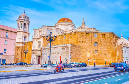 CADIZ, SPAIN - SEPTEMBER 19, 2019: Campo del Sur Avenue leads along the back side of Cathedral with its old sandstone walls with small windows, on September 19 in Cadiz Editorial