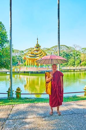 YANGON, MYANMAR - FEBRUARY 17, 2018: The portrait of Bhikkhu monk in red robe with umbrella, posing at the lake and Shrine in Theingottara park, on February 17 in Yangon. 에디토리얼