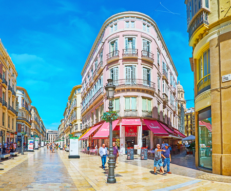 MALAGA, SPAIN - SEPTEMBER 26, 2019: The scenic edifice in Calle Larios with corner half-round facade and restaurant on the ground floor, on September 26 in Malaga Editoriali