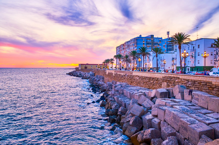 CADIZ, SPAIN - SEPTEMBER 19, 2019: Campo del Sur avenue is nice place for evening walk with a view on Atlantic Ocean, colorful old buildings, bastions of the fortress, on September 19 in Cadiz