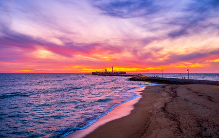 Enjoy the cloudy sunset over Atlantic Ocean with a view on tidal waves, ripples on water and medieval San Sebastian castle with tall lighthouse, Cadiz, Spain Editorial