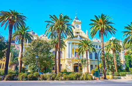 The scenic Town Hall edifice, facing Cervantes avenue and surrounded with lush palm trees, Malaga, Spain