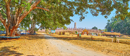 KAKKU, MYANMAR - FEBRUARY 20, 2018: Panorama of the shady park at Kakku Pagodas site with old spread trees, benches and alleys, on February 20 in Kakku. Redakční