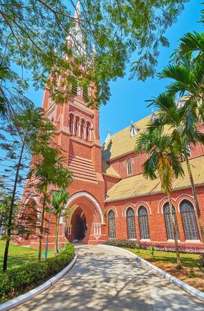 The shady garden alley leads to the tall belfry of Holy Trinity Anglican Church, Yangon, Myanmar