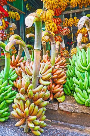 The close-up of red and green bunches of bananas at the street market stall of Chinatown, Yangon, Myanmar