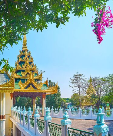 Walk in shady park of Tatmadaw hall and enjoy blooming bushes of bougainvillea and fantastic Burmese architecture, Yangon, Myanmar Stock Photo