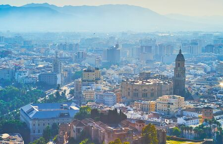 The ramparts of Gibralfaro castle open the view on Malaga old town, covered with haze; the tall bell tower of Cathedral dominates the city, Spain Banco de Imagens