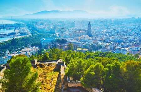 Top view on hazy Malaga city and mountains from the rampart of Gibralfaro castle, Spain