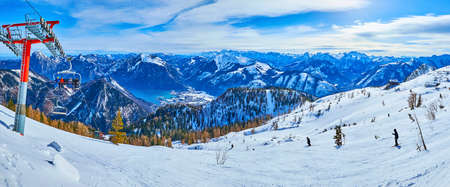 Panorama with snowbound slope of Feuerkogel Mount, modern chairlift, Traunsee lake vallet and rocky Alps of Salzkammergut on the background, Ebensee, Austria Imagens