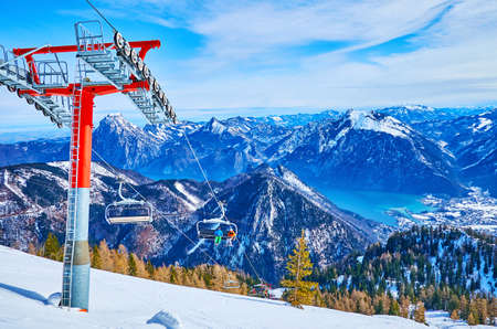 The chairlifts of Feuerkogel Mount offer the breathtaking journeys over the steep snowy slopes and Traunsee lake valley, Ebensee, Salzkammergut, Austria Imagens - 151356806