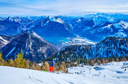 The winter Alpine scenery with a skier, making downhill along the Feuerkogel Mountain slope with a view on Ebensee town in Traunsee lake valley, Salzkammergut, Austria