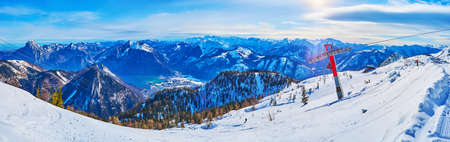 Panorama of Feuerkogel mountain winter resort with cableway, skiers, snowy slopes of Dachstein Alps and Traunsee lake in valley, Ebensee, Salzkammergut, Austria