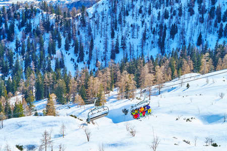 The ski lift cabins, carrying people along the white snowy slope of Feuerkogel Mount, Ebensee, Salzkammergut, Austria Imagens - 151356891