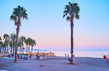 MALAGA, SPAIN - SEPTEMBER 26, 2019: Enjoy the purple sunset on Malagueta beach with a view on calm waters of the sea, tall palm trees and Malagueta sign, on September 26 in Malaga Archivio Fotografico - 134760898