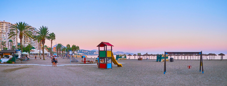 MALAGA, SPAIN - SEPTEMBER 26, 2019: The sunset view on Malagueta beach with tourist cafes and kids playground, on September 26 in Malaga Archivio Fotografico - 134760899
