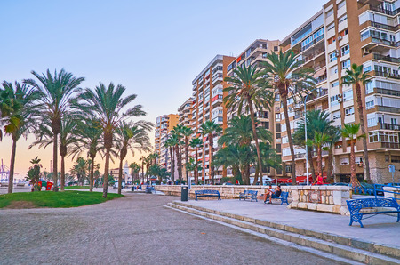 MALAGA, SPAIN - SEPTEMBER 26, 2019: The modern high rises and lush palm trees in Malagueta coastal neighborhood, popular among the tourists and holidaymakers, on September 26 in Malaga Archivio Fotografico - 134760902