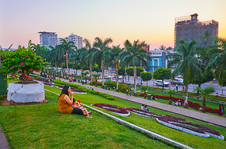 YANGON, MYANMAR - MARCH 2, 2018: Inya lake park boasts juicy green lawn, topiary plants, blooming bushes and colorful flower beds, on March 2 in Yangon Redakční