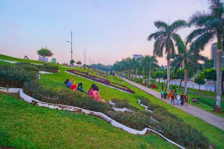 YANGON, MYANMAR - MARCH 2, 2018: People enjoy the sunset in Inya lake park, the best place to have picnic, walk and relax in heart of busy city, on March 2 in Yangon Redakční