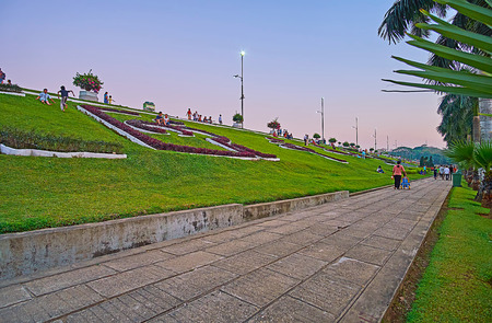 YANGON, MYANMAR - MARCH 2, 2018: Inya lake park in Hlaing district is one of the most popular places for the walks, sport activity, picnics and romantic dates, on March 2 in Yangon.