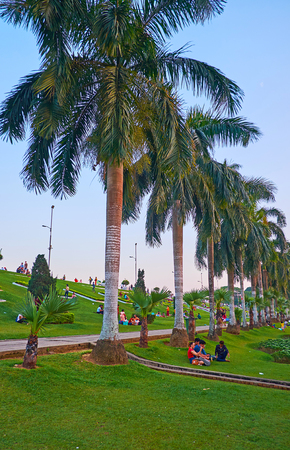 YANGON, MYANMAR - MARCH 2, 2018: People take a rest under the tall shady palm trees in picturesque Inya lake in Hlaing district, on March 2 in Yangon