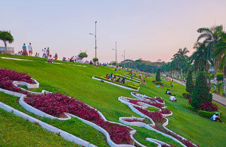 YANGON, MYANMAR - MARCH 2, 2018: People sit on the lawn among the colorful flower beds of Inya lake in Hlaing district, on March 2 in Yangon