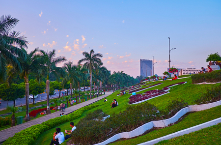YANGON, MYANMAR - MARCH 2, 2018: The evening picninc among the flower beds on the hill in in Inya lake park, the best place to watch the sunset and enjoy the nature, on March 2 in Yangon