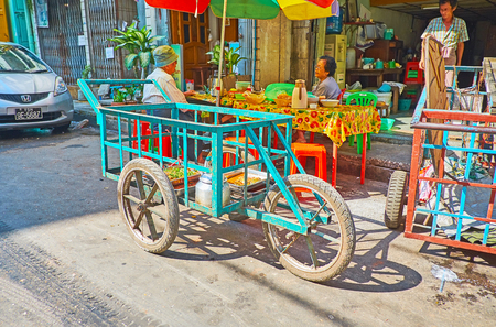 YANGON, MYANMAR - FEBRUARY 17, 2018:  The trolley cart of the food seller, parked at the outdoor cafe in Chinatown, on February 17 in Yangon
