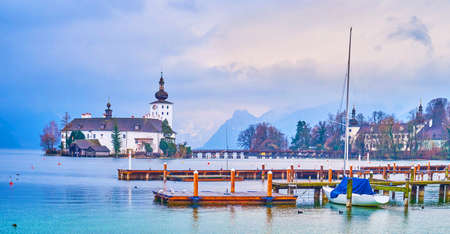 The rainy weather in Gmunden, heavy clouds stuck over Traunsee lake and Seeschloss Ort castle, that is seen behind the shipyard, Salzkammergut, Austria Imagens - 151356915