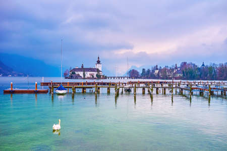 The lonely swan floats at the empty shipyards of Gmunden port on Traunsee lake, the medieval Schloss Ort is seen on the background, Salzkammergut, Austria Imagens - 151356930