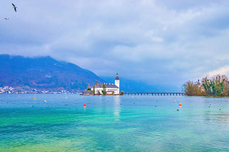The stunning snow-white Ort Seeschloss (lake castle) amid the Traunsee, that is covered with heavy rainy clouds, hovering in Alps around the lake, Gmunden, Salzkammergut, Austria Zdjęcie Seryjne