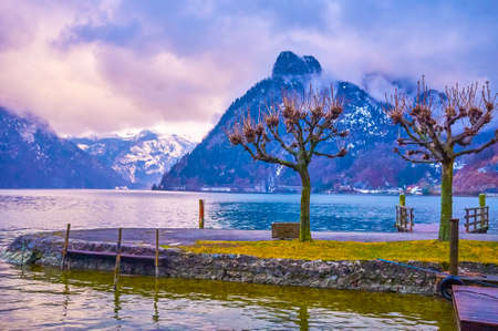 The rainy evening on Traunsee lake with a view on rippled water surface and huge Alpine mountain range, stretching along its bank and covered with heavy clouds, Traunkirchen, Salzkammergut, Austria.