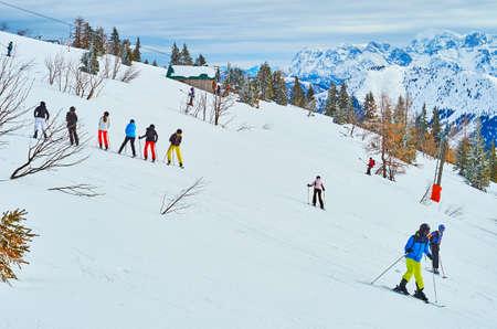 Beginner skiers make their training exercises on the gentle snowy slope on Feuerkogel Mountain plateau, Ebensee, Salzkammergut, Austria Imagens - 151357010