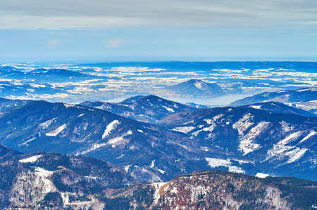 The hazy snowy landscape of Salzkammergut with Attersee lake, hidden behind the rocky slopes, seen from the top of Alberfeldkogel mount, Ebensee, Salzkammergut, Austria Imagens - 151357019