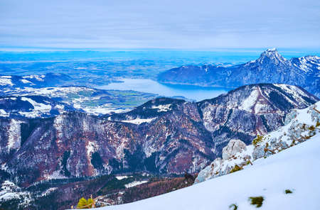 The winter Alpine landscape with a view on Traunsee lake, Traunstein mount with rocky cone and light haze over the land, Alberfeldkogel mount, Ebensee, Salzkammergut, Austria