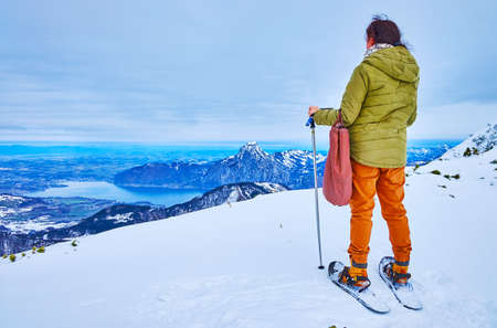 The snowshoer observes the valley of Traunsee lake and cone-shaped Traunstein mountain, standing on the edge of Alberfeldkogel mount on Europakreuz viewpoint, Ebensee, Salzkammergut, Austria