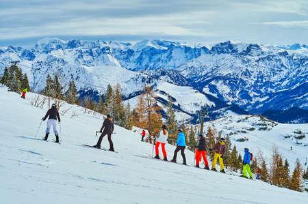 The goup of beginner sportsmen of the ski school on the gentle mountain slope during the training, Feuerkogel Mountain, Ebensee, Salzkammergut, Austria