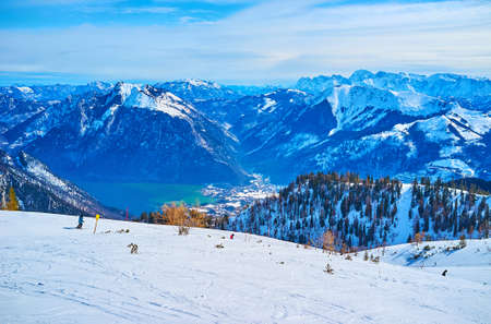 Idyllic winter nature of Alps with a view on snowbound slopes of Feuerkogel Mount and hazy Traunsee lake in valley on the background, Ebensee, Salzkammergut, Austria