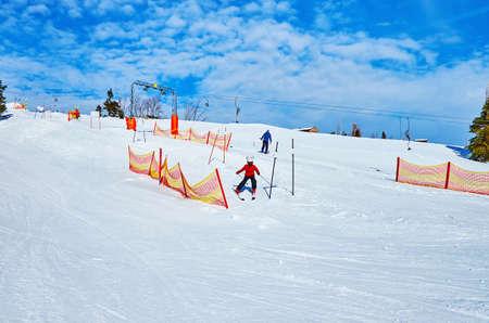 The little boy trains to ski in kids ski zone of Feuerkogel Mountain, Ebensee, Salzkammergut, Austria Imagens - 151357297